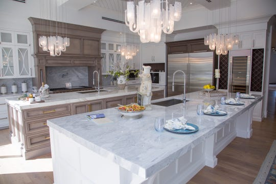 The new Hamptons Luxury Kitchen & Bath showroom on Fifth Avenue South offers full scale kitchen displays such as these eye-catching double islands .