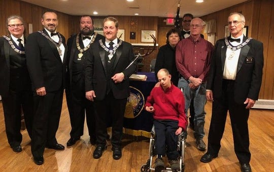 """Joey Pierce, of Verona, was recently installed as a Special Member of the Cedar Grove Elks Lodge 2237. Joey has been involved with the CG Elks for many years at Elks Camp Moore as a camper and also served a year as the NJ State Elks Special Children Committee """"Area Ambassador.""""  Now that he is 21, he can now join as a bona fide member of the lodge. Joey is flanked by the CG Elks' officers who performed the initiation ceremony. Also pictured behind him is his mom Diane and dad Chris, both CG Elks members themselves."""