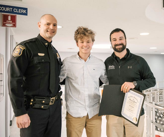 Henry Ford Health System athletic trainer Eric Schwab (right) was recognized by the Hazel Park Police Department for his life-saving effort that revived University of Detroit Jesuit hockey player Conor Place (center) who collapsed and was unresponsive during a December practice. Hazel Park Police Chief Brian Buchholz is pictured on left.