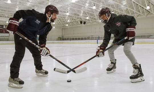 Henry Ford Health System athletic trainer Eric Schwab (left) and University of Detroit Jesuit hockey player Conor Place stage a face-off during a recent Cubs practice.