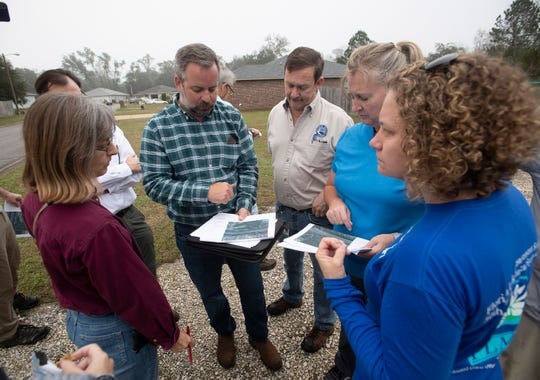 Members of the Restore the Watershed project team compare notes during a tour of Carpenter Creek on Tuesday.