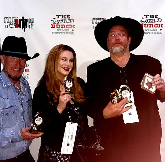 "John Carter Cash, his wife Ana Cristina Cash and Eric Hamilton pose with Wild Bunch Film Festival trophies for ""Dragon Song,"" a film John wrote, produced and won several awards for at the 2019 festival."