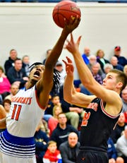 York High's Branden Mutunga, left, takes the ball to the basket while York Suburban's Max Reinecker defends during PIAA District 3, Class 5-A first-round boys' basketball action at William Penn Senior High School in York City, Monday, Feb. 17, 2020. York High would win the game 81-65. Dawn J. Sagert photo