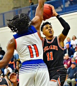 York Suburban's Savon Sutton, right, takes the ball to the basket while guarded by York High's Branden Mutunga during a boys' high school basketball game in February. The possibility of using a shot clock in high school basketball was voted down recently by the National Federation of State High School Associations, which is the country's governing body of high school sports. Dawn J. Sagert photo
