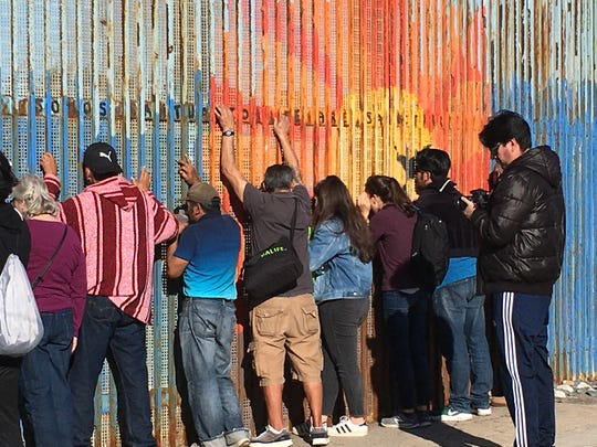 """People on the Mexican side of the border look to """"visit"""" family members through mesh in the wall during Katie Jo Suddaby's trip to the border."""