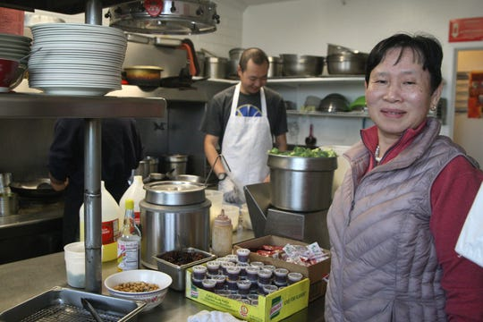 Daisey Tan poses for a photo in the kitchen of her family's restaurant, Cantonese Express Food. In the background stands her nephew, Kevin. Feb. 17, 2020.