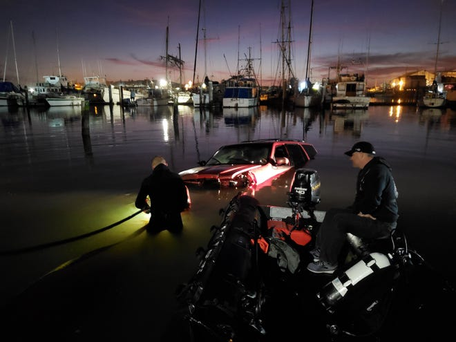 Monterey County Sheriff's Office Public Safety Dive Team members respond to the scene of a crash. A Lincoln Navigator drove off Highway 1, crashed through a fence and into the Moss Landing Harbor Feb. 15, 2020, Monterey County deputies said.