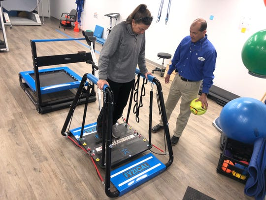 Jenny Corbett tests her balance skills during sessions with Tim Bickford, a physical therapist at Fyzical Therapy & Balance Center.