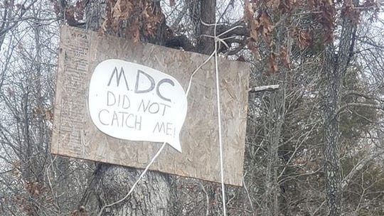 A dead feral hog strung up from a tree in Dent County sends a message to the conservation Department.
