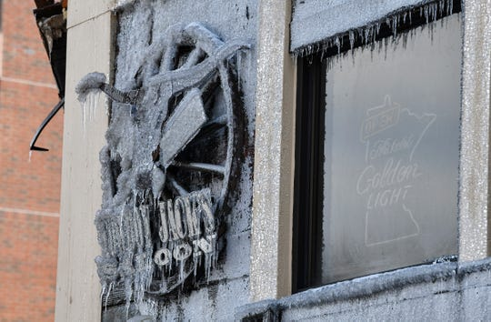 The Cowboy Jack's Saloon sign is encased in ice Tuesday, Feb. 18, 2020, after a fire destroyed the Press Bar next door Monday.