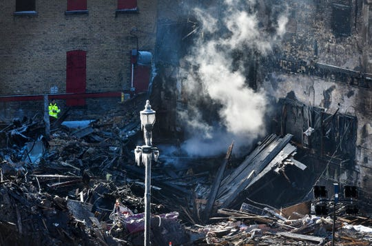 Smoke continued to rise from the rubble at the former location of the Press Bar following a press conference on the blaze Tuesday, Feb. 18, 2020, in St. Cloud.