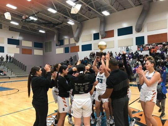 The Pebble Hills girls basketball team celebrates winning a bidistrict championship on Monday night at home against Midland High, 51-45.