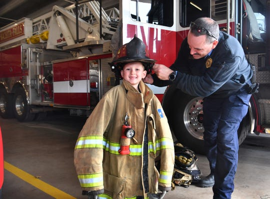 Tucker Hrncirik, 8, tries on a firefighter bunker coat with Captain Chris Duncan at Fire Station 1 Tuesday. The Fowler Elementary second-grader got a Mayor for a Day prize through a school PTO fundraising auction.