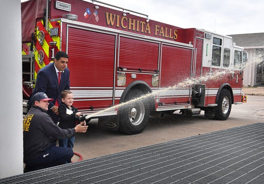Wichita Falls Mayor Stephen Santellana and firefighter Jarrod Nichols help as Fowler Elementary student Tucker Hrncirik, 8, shoots water from a fire hose during a tour Tuesday morning. Hrncirik got to be Mayor for a Day through a school PTO fundraiser auction.