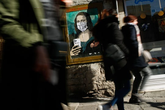 """People walk by a poster by Italian urban artist Salvatore Benintende aka """"TVBOY"""" depecting Leonardo da Vinci's Mona Lisa  wearing a protective facemask and holding a mobile phone reading """"Mobile World Virus"""" in Barcelona, Spain on Feb. 18, 2020, a week after the World Mobile Congress was cancelled due to fears stemming from the coronavirus that sparked an exodus of industry heavyweights."""