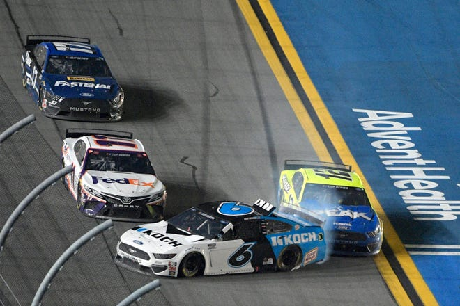 Ryan Newman (6) gets turned into the wall by Ryan Blaney (12) as Denny Hamlin (11) misses them along the front stretch to win the NASCAR Daytona 500.