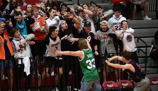Zach Wright, left, and Gibson Boyd, seniors at Powdersville  High School, lead the crowd waving during halftime of the Class AAA Region II playoff game with Broome at Powdersville High School Tuesday.