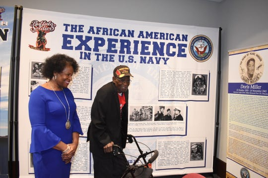 "Charles N. Smith (left), 96-year-old World War II Army veteran, and his daughter Navy veteran Barbara Dashiell-Williams look at the exhibit, ""A Legacy of Honor and Valor,"" at the Alexandria Museum of Art. Four of Smith's seven children served in the military. Two grandsons and a son-in-law are currently serving in the Army."