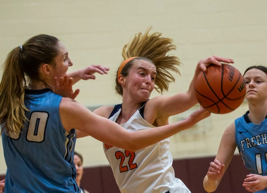 Trinity Hall's Colleen Kelly battles with Hannah Orloff for ball. Trinity Hall Girls Basketball defeats Freehold Township Girls Basketball in SCT opening round game in Ocean Township on February 18, 2020.