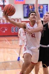 Cooper's Kaden Davis (21) goes up for a shot against Wylie at Cougar Gym on Tuesday. Davis finished with seven points before fouling out in the Cougars 66-54 victory.