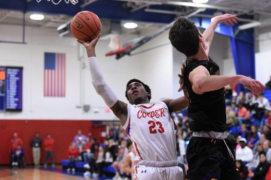 Cooper's C.J. Jemison (23) adjusts in the air to get a shot up around Wylie's Walker Piland (40) at Cougar Gym on Tuesday. Jemison scored 12 points as the Cougars won 66-54 to clinch a playoff berth and set up a seeding game for third place against Wylie on Friday at Abilene High.