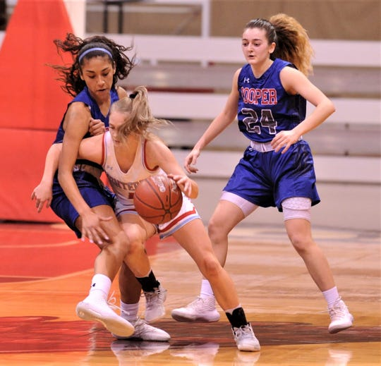 Cooper's Keiana Kemp, left, and Meri Tetaj defend against Lubbock Monterey's Taysha Rushton. Monterey beat the Lady Cougars 77-38 in the Region I-5A bi-district playoff game Tuesday, Feb. 18, 2020, at Howard College's Garrett Coliseum in Big Spring.