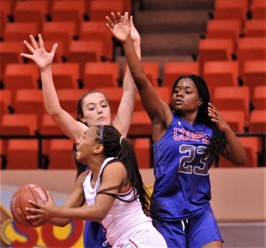 Cooper's Dazz Larkins (23) and Brianna Garcia defend against a Lubbock Monterey player. Monterey beat the Lady Cougars 77-38 in the Region I-5A bi-district playoff game Tuesday, Feb. 18, 2020, at Howard College's Garrett Coliseum in Big  Spring.