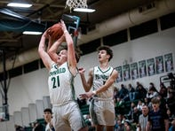 Pennfield junior Shawn Gardner (21) and Pennfield sophomore Luke Davis (4) fight for the rebound on Tuesday, Feb. 18, 2020 at Pennfield High School in Battle Creek, Mich.