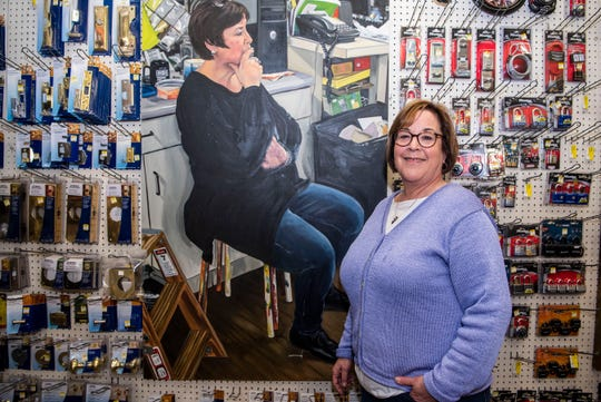 Kerrie Redner, co-owner of Lakeview Hardware, poses for a portrait next to artist Rachel Lussier's painting of her on Feb. 19, 2020 in Battle Creek, Mich. The 90-year-old hardware store is going up for sale.