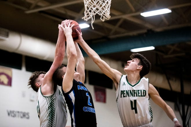 Pennfield junior Shawn Gardner (21) and Pennfield sophomore Luke Davis (4) attempts to take the rebound from Harper Creek senior Wyatt Irons (2) on Tuesday, Feb. 18, 2020 at Pennfield High School in Battle Creek, Mich.