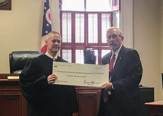 Justice Pat Fischer (right) presents Judge Matthew Schmidt a grant award on Feb. 19, 2020