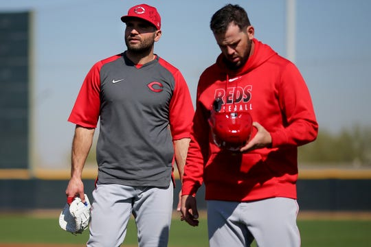 Cincinnati Reds first baseman Joey Votto (19), left, and second baseman Mike Moustakas (9), right walk off the field between drills, Wednesday, Feb. 19, 2020, at the baseball team's spring training facility in Goodyear, Ariz.