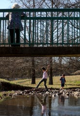 Marilyn Smith, foreground, watches her great granddaughter Courtney Walker, 11, step carefully across the small creek at Valleybrook Park in Clarksville, Tenn., on Monday, Feb. 17, 2020.