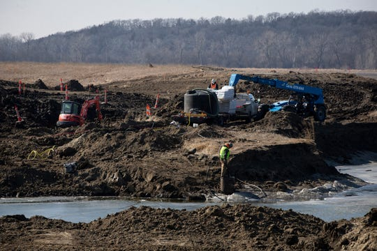 Workers test relief wells in a levee breach near McPaul. Temporary ring levees are being built around the three breaches until a new levee can be constructed.