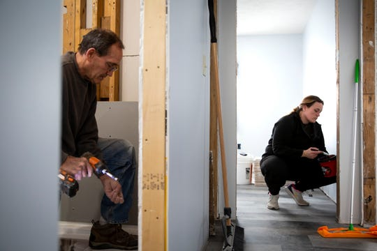 Pacific Junction Mayor Andy Young, left, installs a piece of backerboard as his daughter Clydie Nelsen, right, paints a room at her father's home on Tuesday, Feb. 18, 2020, in Pacific Junction. Almost a year ago, floodwaters were up to the roof of Young's home. He has spent the last year working on his and his daughter's homes, while also trying to help the hard-hit town get back on its feet.