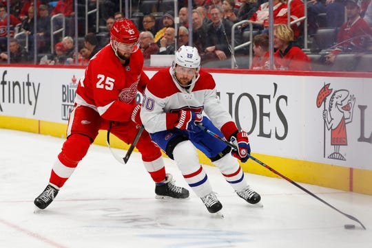 Montreal Canadiens left wing Tomas Tatar (90) protects the puck from Detroit Red Wings defenseman Mike Green (25) during the third period of an NHL hockey game Tuesday, Feb. 18, 2020, in Detroit. (AP Photo/Paul Sancya)