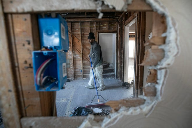 Michael Hill, 55, of Detroit helps sweep up debris from a house undergoing a rehab on Monica Street in Detroit as part of the Fitzgerald neighborhood revitalization project Tuesday, Feb. 11, 2020.