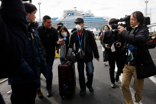 An unidentified passenger is surrounded by the media after he disembarked from the quarantined Diamond Princess cruise ship Wednesday in Yokohama, near Tokyo. Passengers tested negative for COVID-19 started disembarking.