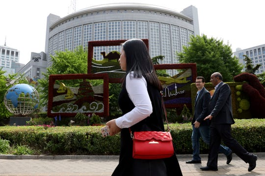 Foreigners pass by the Chinese Foreign Ministry in Beijing.