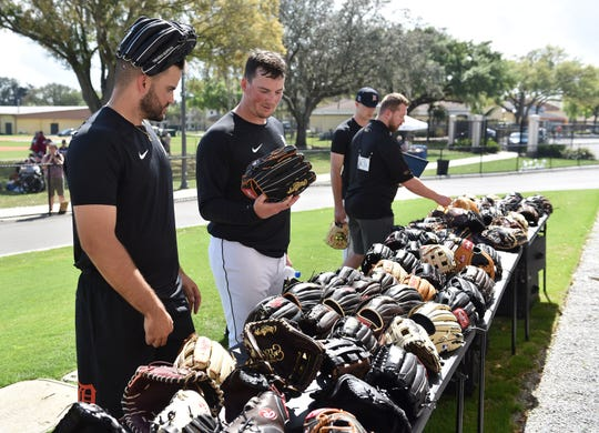 From left, Tigers pitchers Bryan Garcia and Kyle Funkhouser look over the gloves on display by Rawlings outside the clubhouse after the workout.