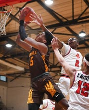 Ferndale's Trey Lewis attacks the basket with Oak Park's Sean Brown Soloman Solo Johnson defending in the third quarter.