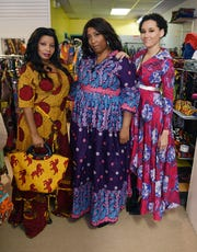 (From left) Models, Foresteen Hood, wearing a maxi wrap dress, Andrea Davis, wearing a maxi wrap dress with puffy sleeves, and Kimmy Kemet, wearing a swing jacket dress.