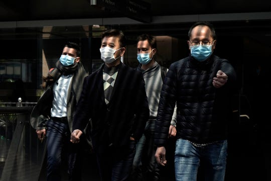 People wearing masks, walk in Central, a business district in Hong Kong, Wednesday, Feb. 19, 2020.