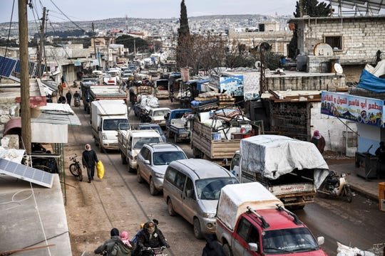 Civilians flee from Idlib toward the north to find safety inside Syria near the border with Turkey, Saturday, Feb. 15, 2020. Syrian troops are waging an offensive in the last rebel stronghold.