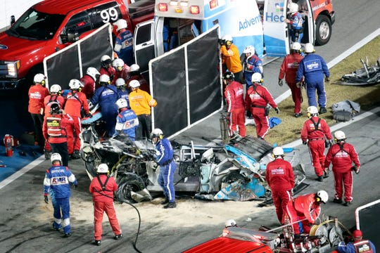 Ryan Newman, left, surrounded by rescue workers is moved to an ambulance after rescue workers removed him from his car.