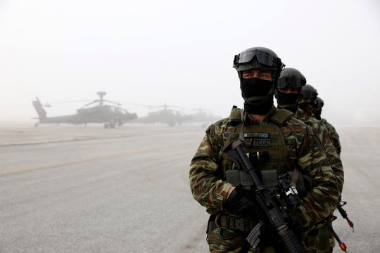 Greek marines stand near helicopters during a drill at a military base in Stefanovikio, central Greece, on Wednesday, Feb. 19, 2020.