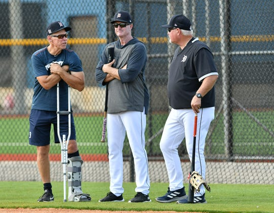 Tigers special assistant to the manager Alan Trammell, left, talks with manager Ron Gardenhire, right, and unidentified coach, center, at Detroit Tigers spring training.   Trammell fractured his fibula in a snowmobiling mishap while riding through trails in northern Michigan with Kirk Gibson.