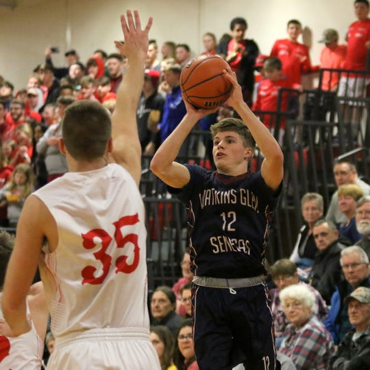 Isaac McIlroy of Watkins Glen goes up for a 3-point try as Waverly's Scott Woodring defends during the Senecas' 60-50 win in an IAC South Large School boys basketball tiebreaker Feb. 18, 2020 at Waverly High School.