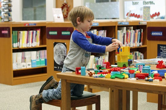 Ari Joy, age 4, concentrates on building the LEGO Coding Express. This will be at the Oak Harbor Public Library until Feb. 25.