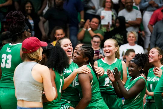 Fort Myer's players and coaches celebrate at the end of their game. Fort Myers beat Dunbar in their Class 6A regional semifinal girls basketball game.